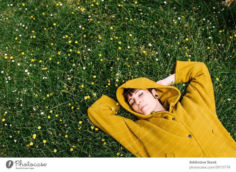 Entspannte ungezwungene Frau liegt auf Wiese sich[Akk] entspannen genießen Sommer Rasen grün Piercing brutal sorgenfrei informell Gras ruhen Natur Blume heiter