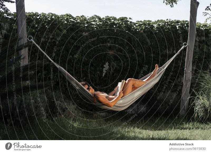 Entspannte Frau mit in Hängematte liegendem Buch sich[Akk] entspannen Kälte Sommer ruhen lesen Lügen Garten Feiertag Urlaub Erholung Lifestyle ruhig genießen