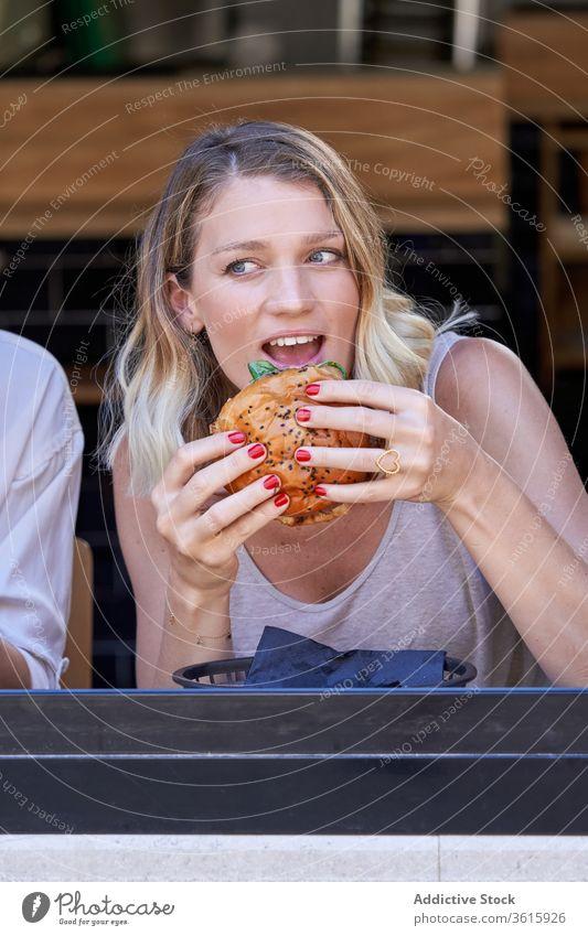Erstaunte Frau beim Essen im Café Mahlzeit aufgeregt Zusammensein Fenster Lifestyle teilen Burger genießen Sitzung Grimasse Mittagessen expressiv Restaurant