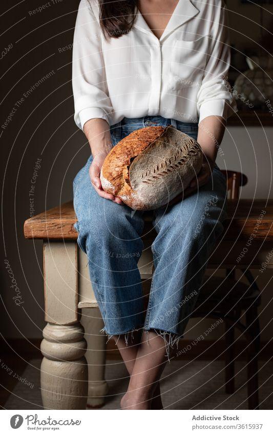 Erntehelferin mit frischem Brot lecker gebacken Frau Küche Bäckerei Tisch Brotlaib Ernährung selbstgemacht heimwärts Gebäck Lebensmittel Tradition sitzen