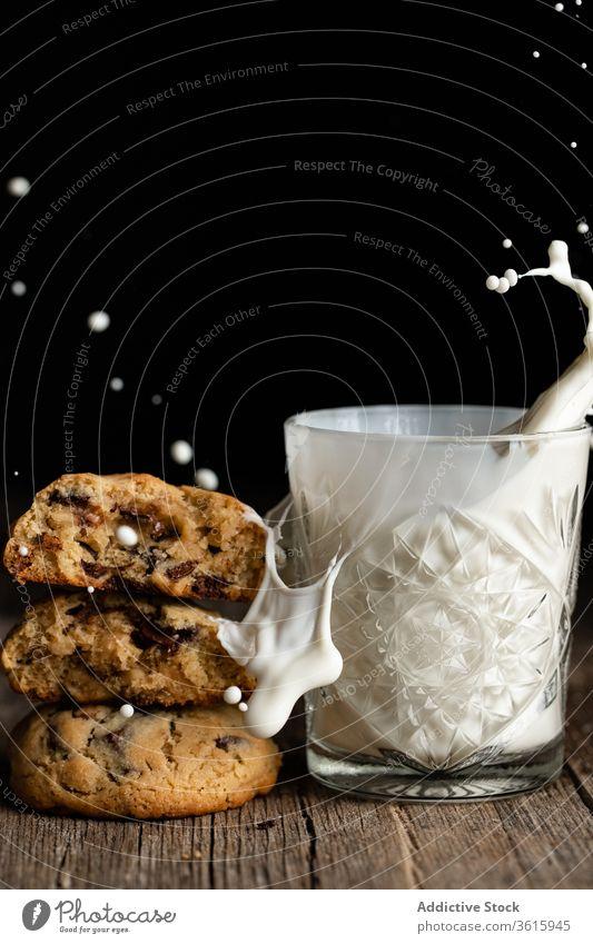 Schokokekse und Glas Milch platschen melken Keks Schokolade Chip hölzern Tisch geschmackvoll Haufen Dessert lecker Lebensmittel trinken Gebäck Snack Zucker