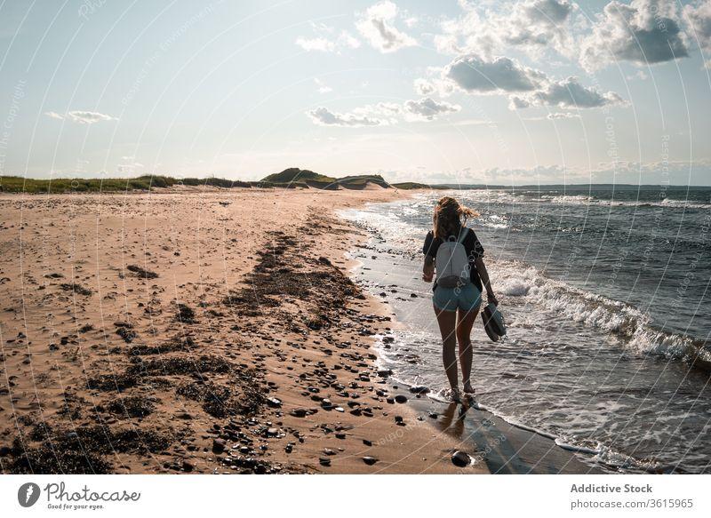 Reisende Frau geht am Meeresufer entlang Spaziergang Seeküste Urlaub Strand Tourist Sommer MEER sonnig reisen Barfuß Feiertag Ausflug Wochenende idyllisch