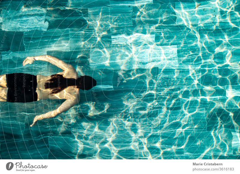 Ein Mann, der allein im Schwimmbad schwimmt, zeigt das Konzept, sich in der neuen normalen Lebensweise aufgrund der Covid-19-Pandemie fit zu halten