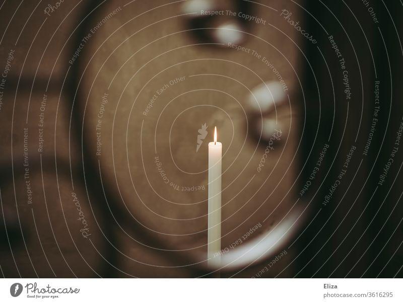Eine brennende lange weiße Kerze in der Kirche hinter einem ornamentalen Gitter Flamme Kerzenlicht Kerzenschein Weihnachten & Advent schlicht Messe Kerzenflamme