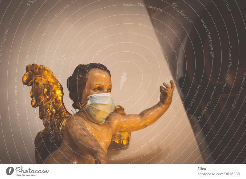 Schutzengel. Ein Engel mit Maske. Schutz vor Corona in der Kirche. Weihnachten. Engelsfigur Gesichtsmaske Mundschutz Glaube Religion schützen kirchlich religiös