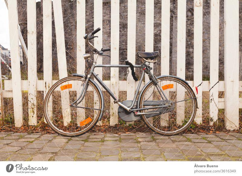 Graues, altes, Vintage- und Retro-Fahrrad, mit Vorhängeschloss an einem weiß gestrichenen Holzzaun in der Stadt Gent, in Belgien, Europa. grau altehrwürdig