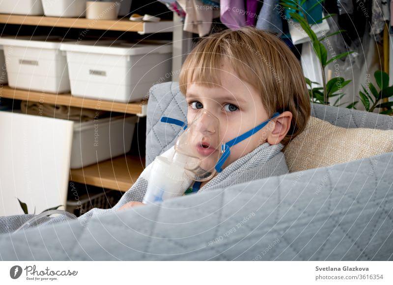 Kleiner kaukasischer Junge, der zu Hause mit einem Vernebler inhaliert. Kind hält einen Maskendampf-Inhalator in der Hand. Behandlung von Asthma. Konzept eines Inhalationstherapiegerätes.