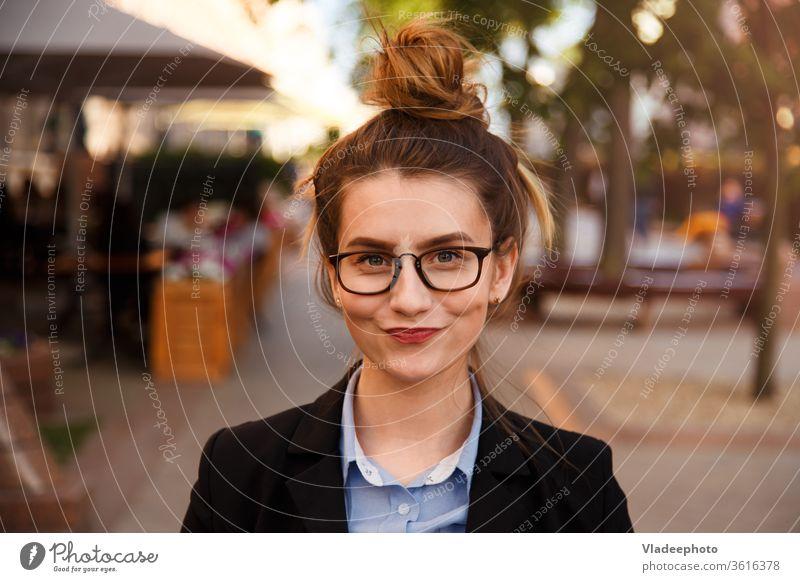 Junge kaukasische Geschäftsfrau mit Brille und lächelnden Lippen. Business Anzug Glück Person Porträt Frau jung schön im Freien Mädchen niedlich Mode hübsch