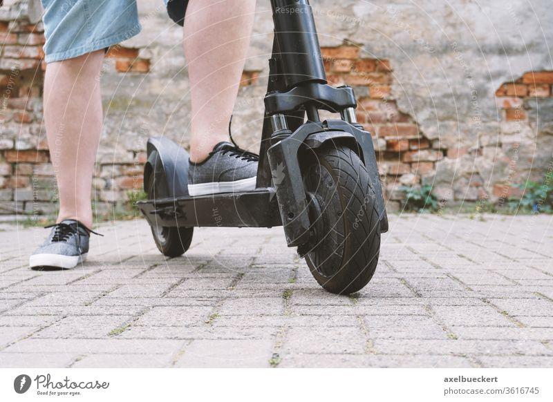 Beine eines nicht erkennbaren Mannes mit E-Scooter E-Roller Tretroller e-Mobilität Mikromobilität Lifestyle trendy Escooter Verkehr elektrisch Person Fuß