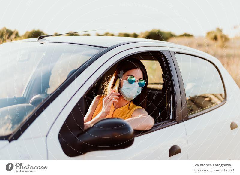 junge Frau in einem Auto, die ein Mobiltelefon benutzt und eine Schutzmaske trägt. Sommersaison. Konzept zur Prävention des Coronavirus PKW Handy Virus