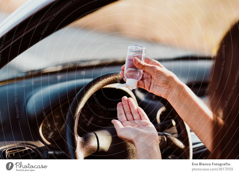 nicht erkennbare Frau, die vor der Fahrt im Auto ein desinfizierendes Alkoholgel verwendet hat. Konzept der sauberen Hände Desinfektionsmittel Gel PKW