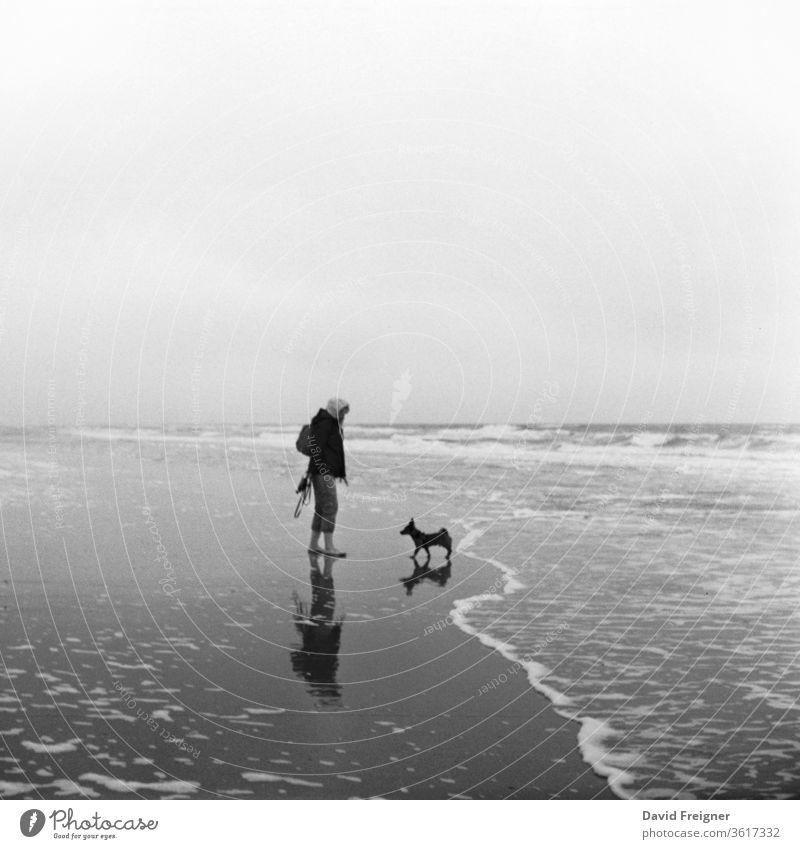 Frau geht mit ihrem Hund an der Nordsee am Strand Gassi und spazieren. Analoge Filmfotografie Meer Sand Wasser Küste Horizont Wolken Wellen Wattenmeer Fernweh