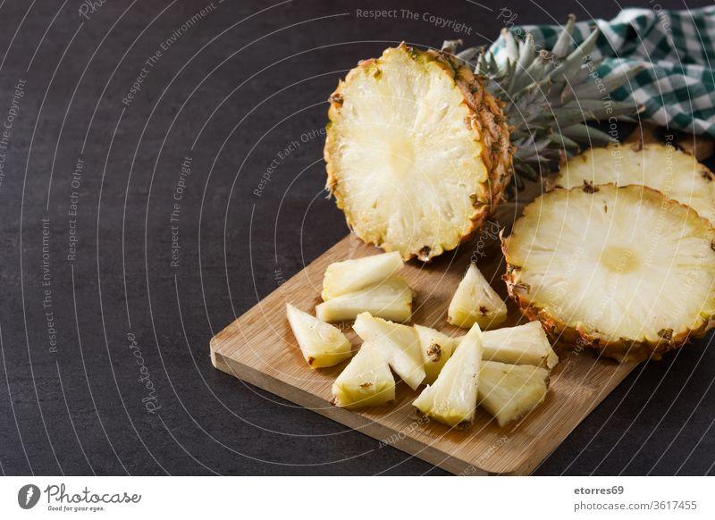 Frische Ananasscheiben auf Schneidebrett und schwarzem Hintergrund. Leerzeichen kopieren geschnitten Dessert Diät frisch Frucht Gesundheit saftig Ernährung