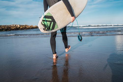 Surfer, der mit seinem Surfbrett ins Wasser geht. Mann Brandung Sport Surfen MEER Meer im Freien sportlich malerisch Küstenlinie Wellen Hintergrund Abenteuer