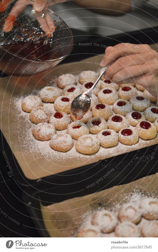Weihnachtbäckerei: Hände einer Frau füllen mit einem Teelöffel Johannisbeergelee in Engelsaugen, auch Husarenkrapfen genannt | Vorfreude Plätzchen Weihnachten
