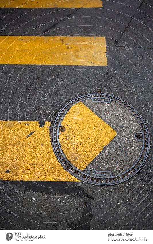 Zebrastreifen und Kanaldeckel Straße Straßenmarkierung Achtsamkeit inkorrekt Fahrbahnbelag gelb grau versetzt Vogelperspektive Asphalt Metall Verkehrswege
