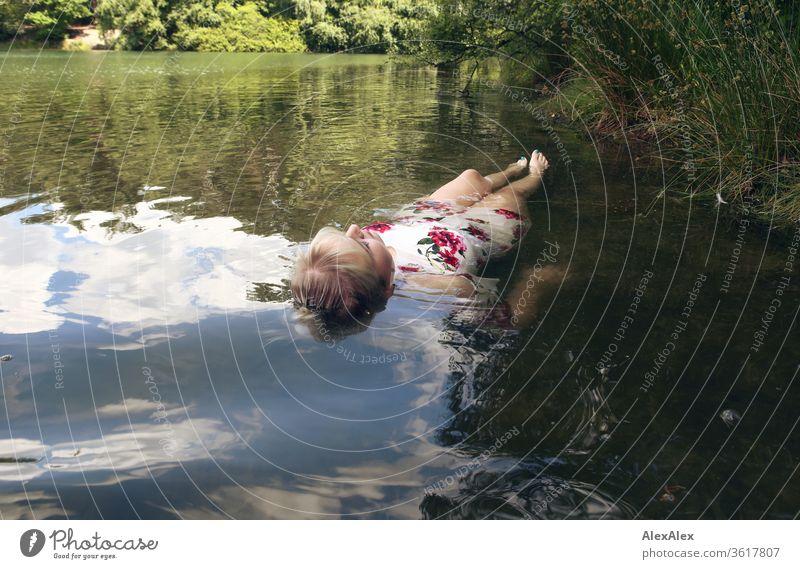 Portrait einer jungen blonden Frau die in einem weißen Sommerkleid in einem See an der Oberfläche Mädchen junge Frau schön lange Haare 19 18-20 Jahre