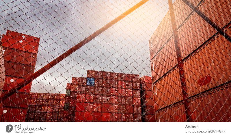 Blick vom Zaun auf gestapelten roten Container. Container-Logistik. Fracht und Versand. Import- und Exportlogistikgeschäft. Container-Frachtbahnhof. Logistische Industrie. Container für Lkw-Transport.