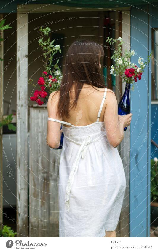 Rückansicht einer jungen Frau in weißem Sommerkleid, hält Blumenstrauß in blauer Glasflasche in der Hand. Partygast im Trägerkleid bringt zur Sommerparty als Überraschung Blumen mit. Junge Braut im Brutkleid.Hippiemädchen bei Sommersonnenwende in Schweden.