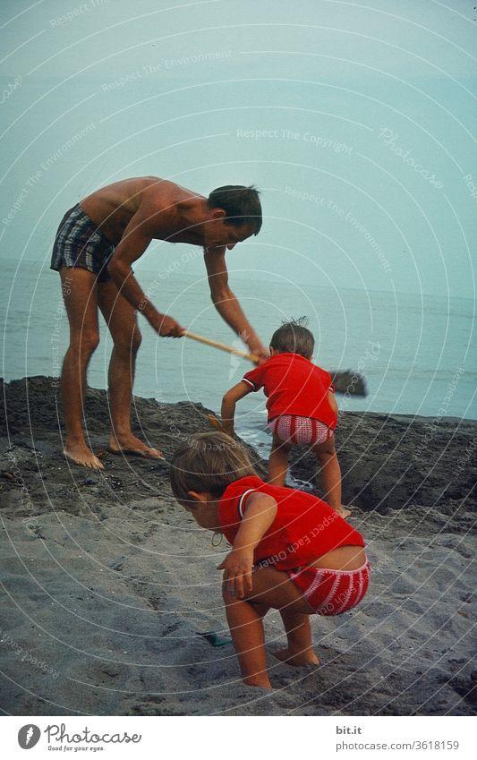 Junger, braungebrannter Papa spielt am Strand mit seinen neugierigen, aktiven Töchtern.Sportlicher, fürsorglicher, vorbildlicher Vater gräbt am Meeresstrand mit seinen kleinen Kindern, einen Graben. Sommertag mit Aktion, Entdeckung und Bewegung im Urlaub.