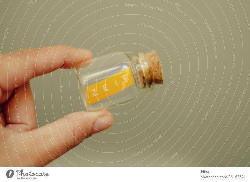 Eine Hand hält ein Glasfläschchen mit dem geschriebenen Wort Zeit darin konservieren Zeit nehmen wertvoll Fürsorge Zeit haben Vergänglichkeit halten