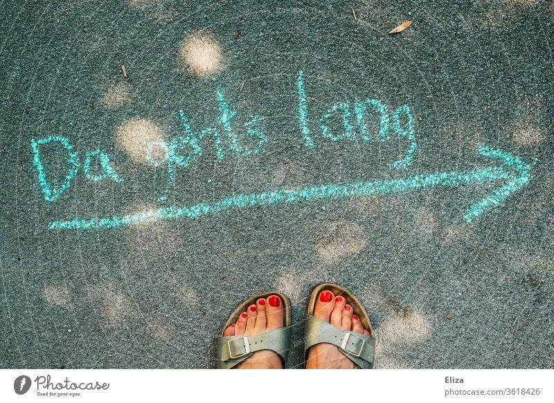 Richtungsweisender Pfeil mit Kreide auf die Straße gemalt und weiblichen Füßen Wegweiser Schnitzeljagd Wege & Pfade Orientierung richtungsweisend zielorientiert