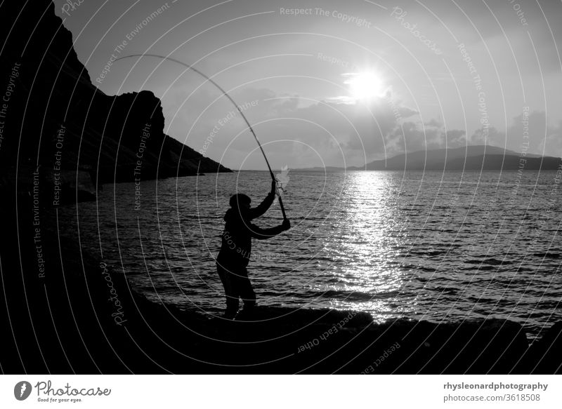 Junger Mann fischt mit Federn auf Makrele B+W Insel Mull Schottland schwarz weiß schwarz auf weiß Fischen Fischerfedern Angelrute Stab Linie Jagd Sport