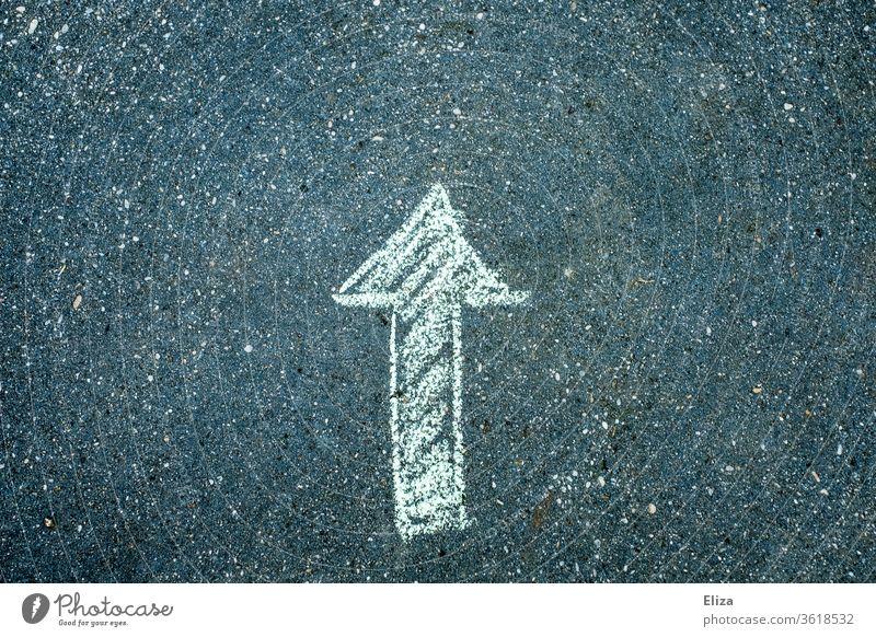 Ein Pfeil der nach oben zeigt mit Kreide auf Asphalt gemalt aufwärts vorwärts Ziel zielgerichtet orientierung Richtung richtungweisend Zukunft positiv