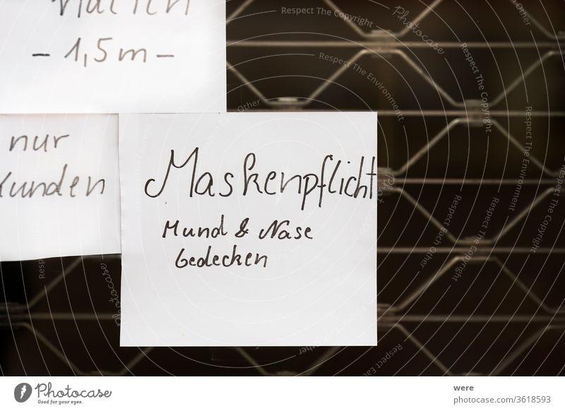 handgeschriebenes Türschild auf einer Eisengittertür mit deutschem Text Maskenpflicht Mund und Nase bedecken Deutscher Text Regelung Korona Deckung Seuche