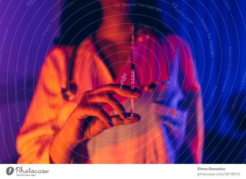 Arzt mit COVID-19, сoronavirus Impfstoff in der Spritze, der zur Vorbeugung von Infektionen im ultravioletten Neonlicht verwendet wird. Konzept für Medizin und Gesundheitsfürsorge.