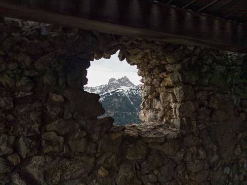 Alte Steinmauer mit Aussicht auf einen Berg. Burg oder Schloss Burgruine Öffnung Loch Steine alt Berge u. Gebirge Licht historisch Ruine Mauer Sehenswürdigkeit