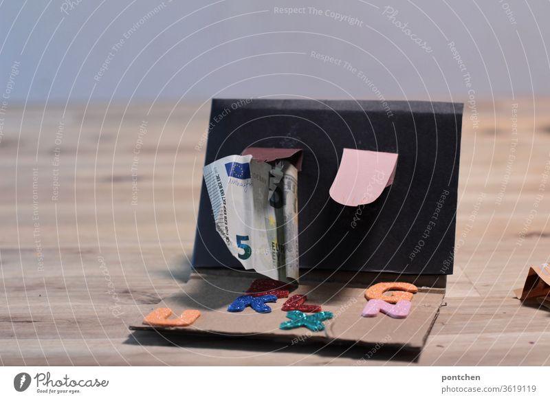 Hände in unterschiedlichen Hautfarben ragen  aus einem Computerbildschirm. Eine Hand hält einen 5 Euro Schein. Bastelarbeit. Profit. Neue Medien hand Finanzen