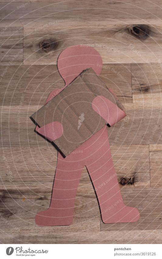 Mensch aus Papier  hält ein Stück leeren Karton, Pappe vor seinem  Körper. Platz für Text . Paket. Paketbote. Demonstration beschriften person text papier