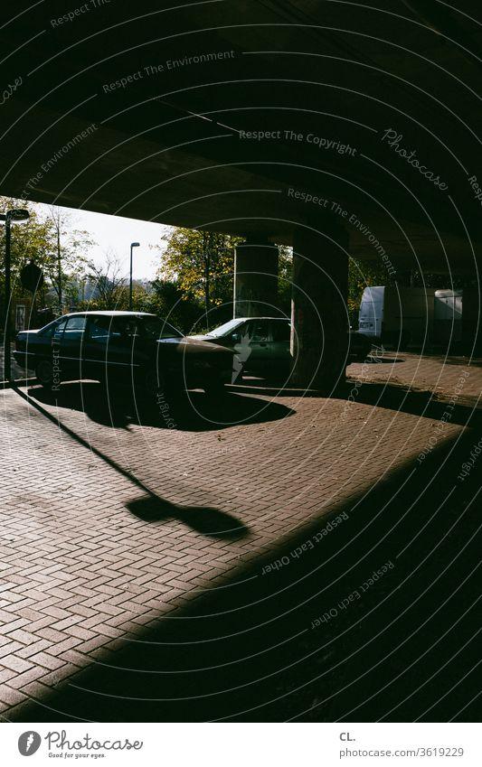 tatort Parkplatz Auto parken Verkehr Straßenverkehr PKW Verkehrsmittel dunkel Fahrzeug geheimnisvoll Stillstand Brücke Schatten Menschenleer Außenaufnahme
