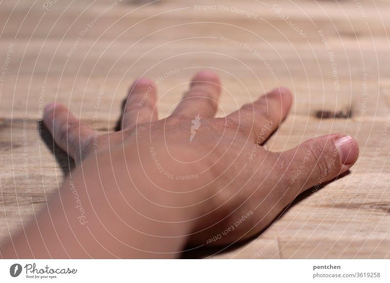 Eine linke,  weibliche, braungebrannte Hand  mit gespreizten  Fingern liegt auf einer Tischplatte  aus Holz.  Dominanz hautfarbe finger tischplatte fingernägel