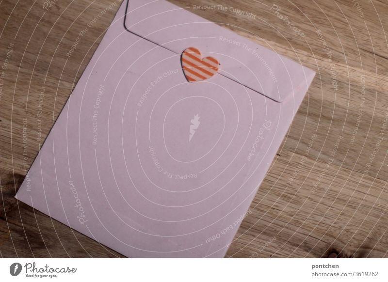 Ein rosa Briefumschlag Großbrief zugeklebt mit einem Herz- Liebesbrief.  Post briefumschlag herz großbrief post romantisch verliebt umwerben geständnis