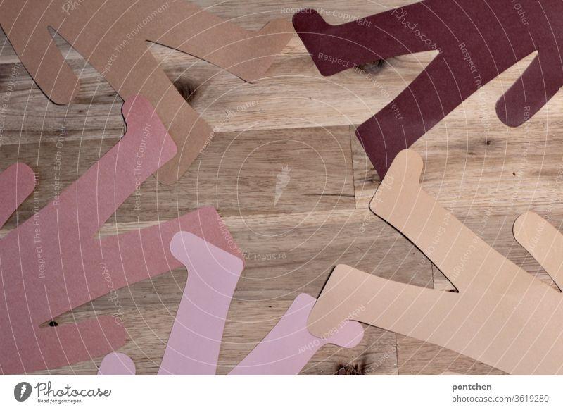 Unterkörper von Menschen aus Papier mit unterschiedlichen Hautfarben liegen im Kreis Fuß an Fuß. Vielfalt, Zusammenhalt, Frieden, Freundschaft hautfarbe