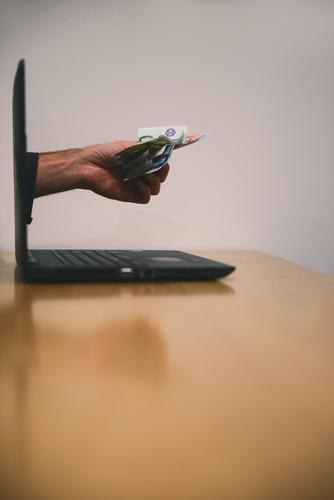 Eine Hand voll mit Geld durchbricht den Laptop Computer Angebot Euro Geldscheine arbeiten auslage Betrug Internet locken onlinebanking Summe Textfreiraum