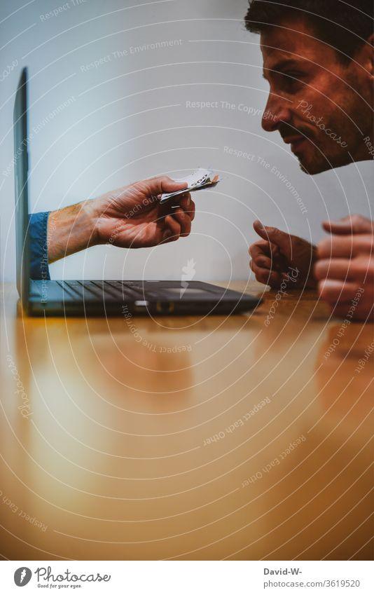 Mann sitzt vor dem Compter und beobachtet eine Hand mit Geld die aus dem Laptop herauskommt. Computer Angebot Euro Geldscheine arbeiten auslage Betrug Internet