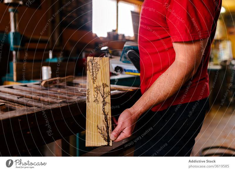 Männlicher Holzarbeiter mit verziertem Holzbrett Tischlerin Werkstatt Pyrograf Pyrographie Mann Kunstgewerbler Kunsthandwerker Schiffsplanken