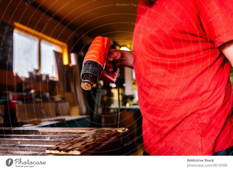 Ernte-Holzarbeiter mit Heißluftpistole in der Werkstatt erwärmen Pistole Schreinerei Tischlerin Mann trocknen Zimmerer Holzarbeiten professionell männlich