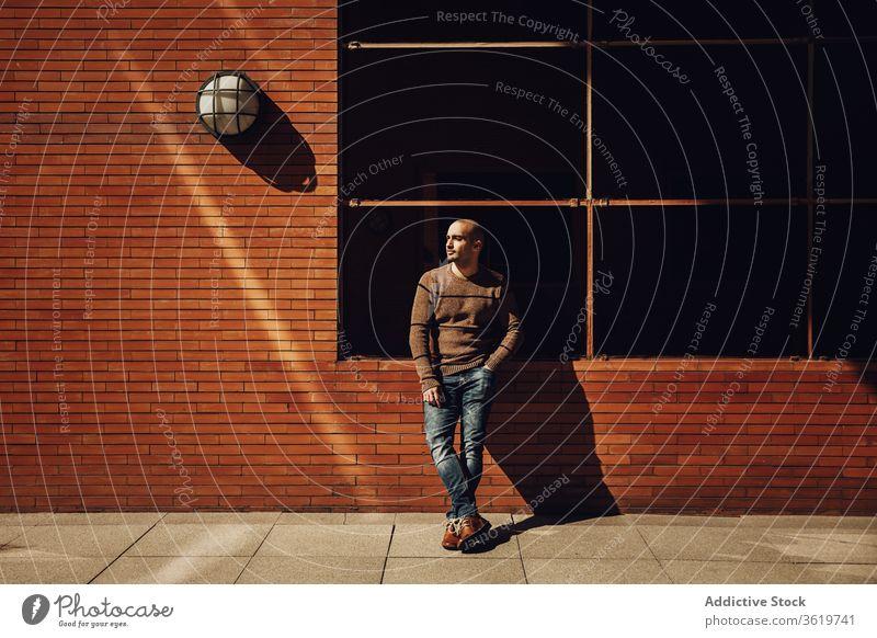 Stilvoller junger Mann steht neben Gebäude selbstbewusst lässig modern kahl Wand urban Straße männlich Trägerkleid Sweatshirt Jeanshose trendy Typ Zeitgenosse
