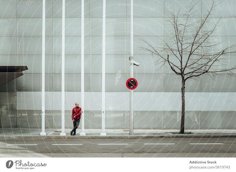Junger Mann steht in der Nähe eines modernen Gebäudes jung Stil lässig Wand urban Straße trendy verbieten Zeichen männlich Zeitgenosse allein Youngster