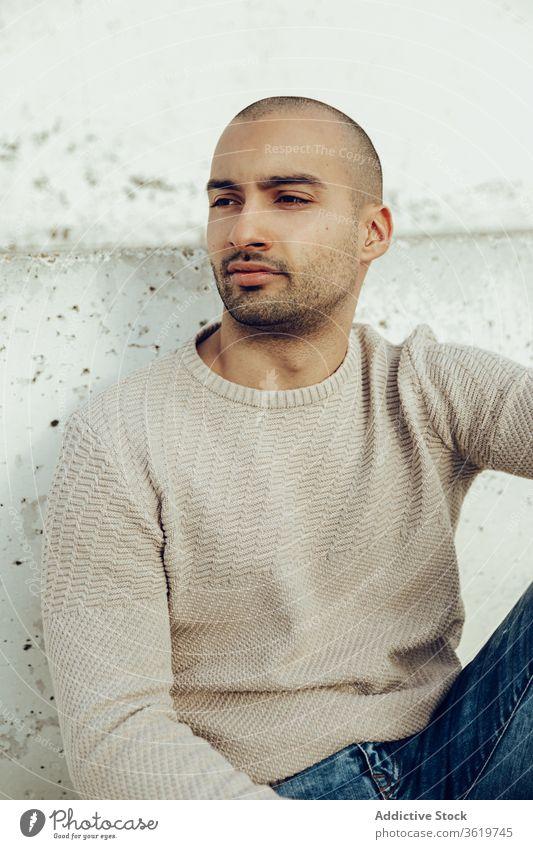 Stilvoller junger Mann sitzt auf Betonwand trendy besinnlich Hipster modern Streetstyle nachdenklich Porträt nachdenken unrasiert Typ Jeanshose sitzen lässig