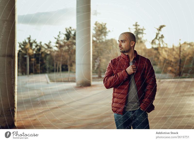 Junger Mann in modischem Outfit steht auf der Straße jung modern selbstbewusst Jacke warme Kleidung besinnlich Hipster unrasiert Herbst Vollbart nachdenklich