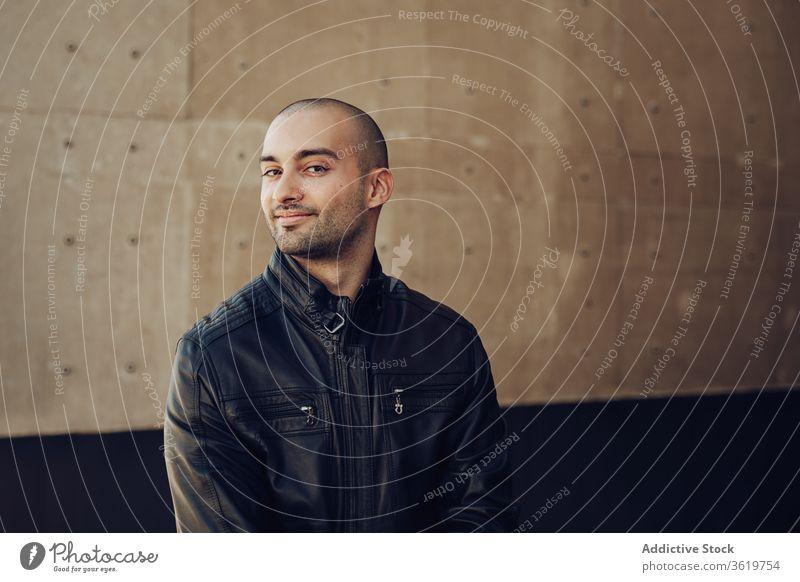 Stilvoller junger Mann steht neben Gebäude selbstbewusst lässig modern kahl Wand urban Straße männlich schwarz Jacke trendy Typ Zeitgenosse gutaussehend Glück