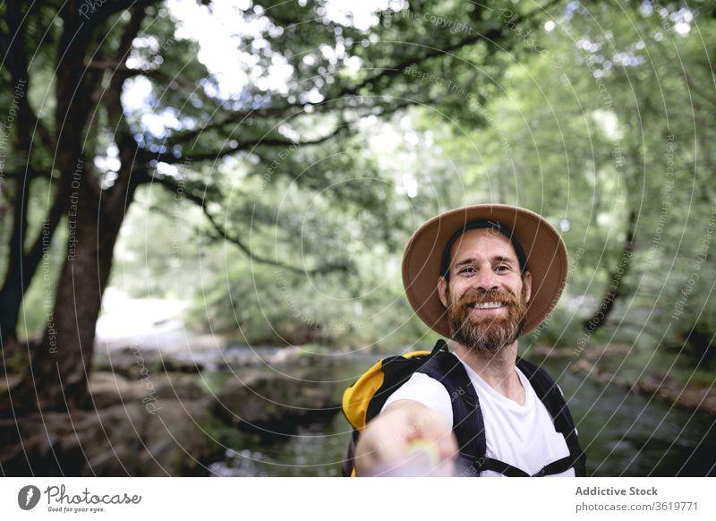 junger Mann mit Bart wandert an einer Seeroute mit Bäumen und schattigen Stellen entlang und nimmt eine Selfie reisen Natur Abenteuer im Freien wandern