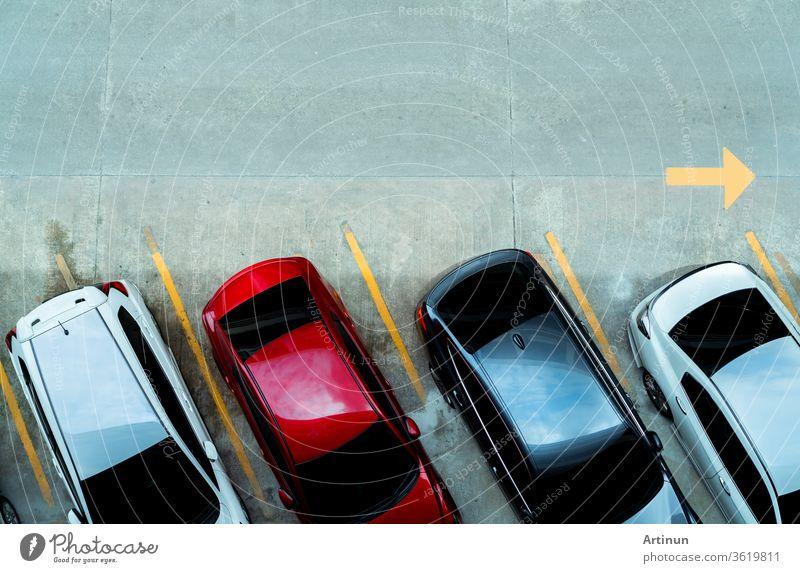 Draufsicht auf ein auf einem Betonparkplatz geparktes Auto mit gelber Linie des Verkehrsschildes auf der Straße. Draufsicht auf das Auto in einer Reihe auf dem Parkplatz. Kein freier Parkplatz. Außerhalb des Parkplatzes.