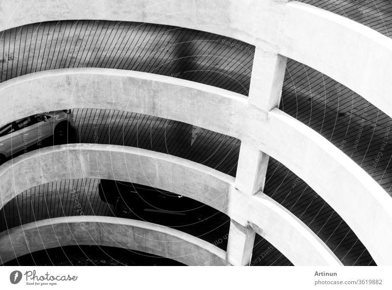 Die Architektur der Spiralkurve und des geneigten Weges zum Parkplatz des Einkaufszentrums. Auto fährt auf Betonstraße auf dem Gebäude des Einkaufszentrums zum Parkplatz.