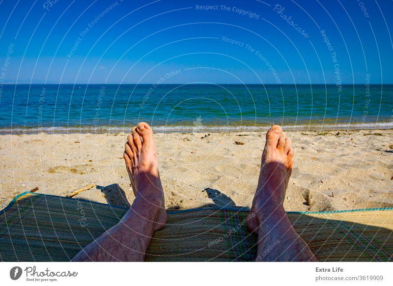 Männerbeine am Strand, Entspannung am Sandstrand Erwachsener Windstille sorgenfrei Küste Küstenlinie farbenfroh genießen Fuß schäumen Feiertag idyllisch